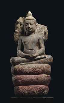 A SANDSTONE FIGURE OF BUDDHAMUCHALINDA THAILAND, LOPBURI PERIOD, 13TH CENTURY Seated in sattvasana on a triple coiled snake, its seven heads originally forming a canopy, both hands resting on his lap in dhyanamudra, wearing samghati leaving his right shoulder bare, his face with serene expression with downcast eyes below ridged eyebrows, smiling lips, elongated earlobes and his hair combed into the ushnisha, traces of gilt, red and black lacquer, on wood stand 35 3/8 in. (90 cm.) high