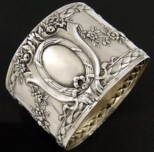 Antique French Sterling Silver Napkin Ring Musical Motif. A gorgeous antique French sterling silver napkin ring, festooned throughout with ornate rose garlands, ribbon bows and further accented by borders of Grecian laurel leaves! What makes this even more beautiful are the two interlocking allegorical embellishments featuring musical instruments to one side and a bow crisscrossing a quiver of arrows on the opposite side of the napkin ring. From The Antique Boutique on Ruby Lane
