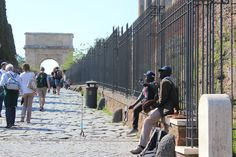 Two street salesmen try to sell selfie sticks in front of the #ArchofTitus