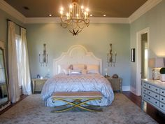 This refined and sophisticated bedroom exerts romance through its use of soft, neutral hues and fabrics paired with antique furnishings and an elegant, oversize fabric headboard. Design by HGTV fan cherrybounce