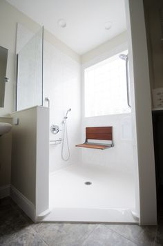 Bathroom Remodel - Walk in shower - with no threshold - handicap accessible shower - white tiled shower, shower seat, multiple shower heads, window in the shower - brought to you by Re-Bath of the Triangle