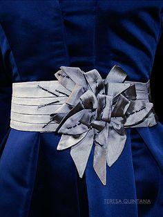 Fajín de pliegues con superposiciones de hojas y pétalos con apliques en canutillo.