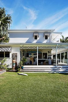 "Kimberly and Stephen's Byron Bay beach house:Fretwork around the verandah was designed to represent the family. ""The cross being Stephen and I, and the three posts in between are the boys,"" says homeowner Kimberly. ""The palms are all handmade; the house is called Little Palm."""