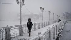 A woman walks over an ice-encrusted bridge in Yakutsk. Oymyakon lies a two day drive from the city of Yakutsk, the regional capital- Welcome to The Coldest Place Inhabited By Humans on Earth