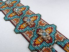 This bead woven cuff was also completed on my loom. The center medallions are actually woven on the loom, within the same plain as the base of the cuff, but additional beads were included to create lifted dimension. The finish incorporates two clasps, as noted with the two strips of beading.