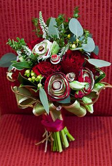 Bouquet of roses, hypericum berries, variegated parrot tulips, veronicas, seeded eucalyptus, boxwood boughs, kiwi branches, and magnolia leaves, accented with satin flowers and button flowers; Floral design by Kio Kreations; button flowers by RBK Creations