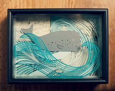 handcrafted paper cut out layered in a shadow box.
