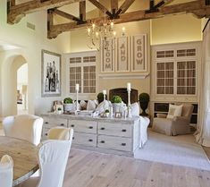 living rooms - Aidan Gray Graceful Elegance Candle Chandelier glass-front built-in cabinets flanking fireplace vaulted ceiling rustic wood beams gray washed console table cabinet white sofa linen club chairs