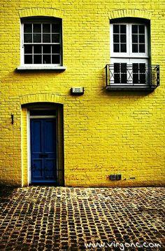Het blauwe deurtje en de knal gele muur van het huisje.