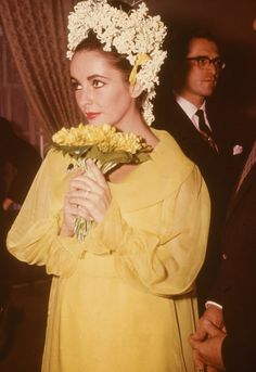 "The same year she divorced Fisher, Taylor wed her ""Cleopatra"" co-star Richard Burton. They were married at the Ritz-Carlton Hotel in Montreal and she wore a short, sunflower yellow chiffon dress, flowers in her hair and an emerald brooch Burton bought her. The couple were divorced in 1974"