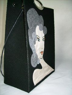 Bag with Lady's portrait is made of black synthetic felt. Woman's face is painted on silk, hair are cut out from gray felt. You can hold her in hand or hang on the should...