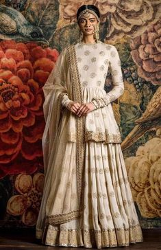 Cream Lehenga with booti printed work and a long simple blouse. Pairing the two together makes the outfit look like an Anarkali. Indian Gowns Dresses, Indian Fashion Dresses, Dress Indian Style, Indian Designer Outfits, Pakistani Dresses, Eid Dresses, Designer Bridal Lehenga, Bridal Lehenga Choli, Lehenga Blouse