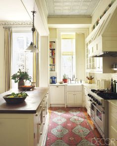 In a New York kitchen decorated by Sheila Bridges, the countertops are of teak and Calacatta marble, the range is by Viking, and the sink and fittings are by Waterworks; the light fixture is antique, and the felt rug is by Liora Manne.