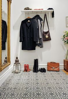 Beautiful, uncluttered entryway w/ white walls & patterned black & white tile floors. A full size gold framed mirror & a hanging shelf for coats finish this roomy entry.