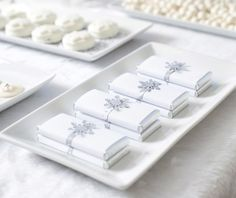 white Christmas dessert table - love the chocolate bars wrapped in white and a silver snowflake...beautiful!
