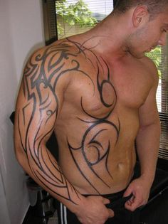 A fresh half body Tribal Tattoo on a guy with muscles.