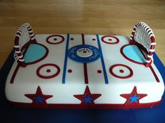 Hockey Rink - A hockey rink cake for friends anniversary Marc and Francois who loves to play hockey together. This is a vanilla cake with buttercream and raspberry jam filling, all covered with fondant.The center logo was hand painted. Everything edible except for the red parts of the goals wich I put wire in.