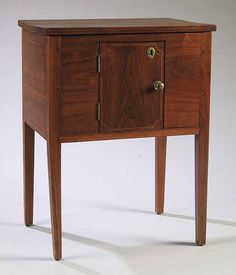 A Southern Federal Inlaid Walnut Cellarette in the Hepplewhite Taste, late 18th c., the lift top opening to yellow pine divided sections, the front with a door opening to a compartment, raised on square tapered legs, door, sides & legs with string inlay. Note: The use of a central door set with a reverse grain seen in this example is also used in other known pieces of Southern case furniture, notably a pine huntboard from Harris Co. Georgia illustrated The Magazine Antiques, May 1976, p. 654