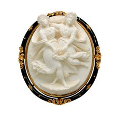 Antique Enamel and 18K Gold Lava Cameo Brooch, circa 1880  The oval black enamelled frame decorated with applied foliate motifs and centering a high relief white lava cameo depicting two nymphs with floral attributes