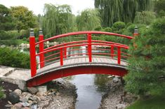 Another instance of a smaller wooden garden bridge in bold Chinese red. The bridge spans the gap between two higher points over a narrowing stream connected to a pond. Pond Bridge, Garden Bridge, Garden Pond, Asian Garden, Chinese Garden, Zen, Japanese Garden Design, Japanese Fence, Japanese Style