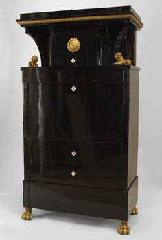 Austrian Biedermeier (Circa 1820) ebonized secretary cabinet with gilt trim and carved lions on either side of ½ round upper section with a drop front veneered with myrtle wood Price $67,500.00