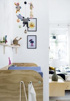 Sweet kids room with a mobile of wooden beads and small teddy bears.