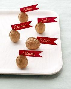 Holiday place setting: walnuts with tiny red banners with gold pen. also cute when the walnuts are spray painted gold.
