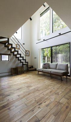 吹き抜けに面した大きな窓からは、明るい光が降り注ぐ。階段下のスペースは、床面が下がっているので、階段したでも高さを確保でき、お子さんの遊び場として使える土間。