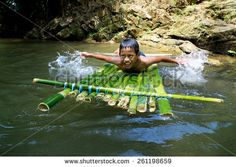 Kiulu, Sabah Malaysia - March 17, 2015: An unidentified boy plays with bamboo raft in the river at interior of Sabah Malaysian Borneo. During dry season kids play in the river is a common view.