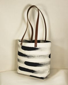 "A super sturdy large natural canvas tote bag with a hand painted stripe in rich black ink. Black or brown leather straps with a 12"" drop. Interior pocket for easy access to your phone and wallet. Each bag is printed, cut and sewn by hand in SF.16"" wide, 12.5"" tall and 4.75"" deep"