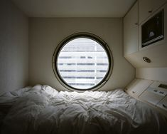 The room was so small that the bed took up most of the room. Lay against the far wall horizontally with a circular window slightly above. On the whole right side on the room with the bed shoved up against lay the cabinets were I assumed food, clothes, and other things were kept...