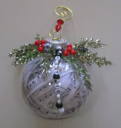 """This ornament was made from """"O Holy Night"""" sheet music, beads that spell the name of the piece, greenery and red and black beads."""