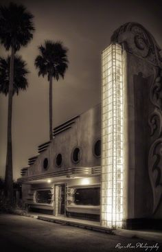 Art Deco building at night, with a column of lighted glass bricks.