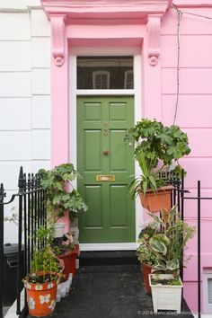 Check out this post from A Lady in London to see the most beautiful homes in all of London. The bright green door and pink entryway of this home make it stand out from miles away. Potted plants help to further accent this house's vibrant color scheme. |@aladyinlondon