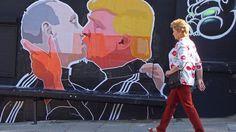 Una mujer pasa frente a un mural en el que Trump y Putin se besan
