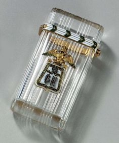 A JEWELLED GOLD AND ENAMEL ROCK-CRYSTAL CIGARETTE-CASE marked Fabergé and with the workmaster's mark of Michael Perchin, St. Petersburg, circa 1896. Of upright rectangular form with rounded corners, the rock-crystal carved with reeded design, the front applied with a gold cast and chased rose-cut diamond set replica of the third Elizavetgrad Hussar Regiment of Her Imperial Highness Grand Duchess Olga Nikolaevna, with diamond thumbpiece