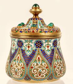 A Russian silver gilt and cloisonné enamel jar, Antip Kuzmichev, Moscow, 1896-1908. Of circular form with raised lobed panels, the box enameled in stylized multi-color foliate motifs outlined by bands of turquoise enamel beads, the shaped domed cover with bezel-set green hardstone cabochons similarly decorated. #antique #vintage #box