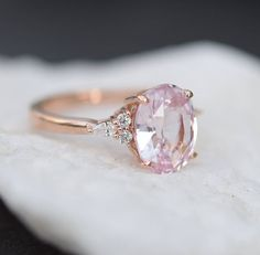 Jaw-Dropping Sapphire Engagement Rings For The Modern Bride ~ EidelPrecious' blush sapphire engagement ring set in 14k rose gold and accented by 2 round and 1 pear diamond on each side of the center stone