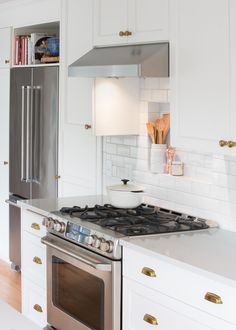Cute tile shelf behind the range in a traditional all-white kitchen with quartz countertops and brass hardware. Magnolia Kitchen designed by Distinctive Kitchens Seattle White Kitchen Decor, White Kitchen Table Set, All White Kitchen, White Ikea Kitchen, White Kitchen Tiles, Black Kitchen Countertops, White Kitchen Accessories, Kitchen Design, Magnolia Kitchen