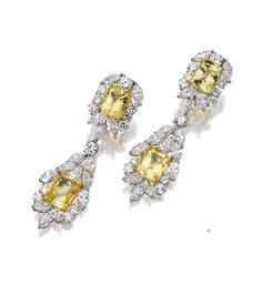 PAIR OF YELLOW SAPPHIRE AND DIAMOND EARCLIPS.  The tops and pendants set with cushion-shaped yellow sapphires together weighing 32.66 carats, framed by 24 round, 24 marquise-shaped and 6 pear-shaped diamonds weighing a total of approximately 21.85 carats, mounted in platinum and 18 karat yellow gold.