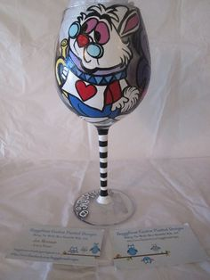 """Custom painted """"Alice In Wonderland"""" themed wine glass finished and headed to a customer in New Hampshire! This glass features Alice, the White Rabbit and the Cheshire Cat! :) https://www.facebook.com/buggybeandesigns"""