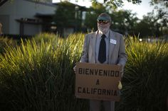 """A man holds a sign at a vigil in support of refugee children and their families in Murrieta, California July 9, 2014. Murrieta has been at the heart of an immigration debate over where to hold and process the surge of illegal migrants crossing the border from Mexico in recent months. The sign reads, """"Welcome to California."""" REUTERS/Lucy Nicholson"""