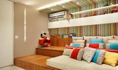 Um tablado em dois níveis, com gavetões: o primeiro degrau apoia a cama-tatame e abriga no gavetão sob ela uma cama auxiliar; o segundo é um espaço para leitura e brincadeiras, com um gavetão para guardar os brinquedos da criança e um vão entre a parede e a marcenaria para guardar livros.