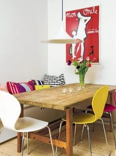Rustic table, mismatched chairs, cushions on bench against the wall, lighting fixture