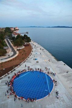"""The coastal town of Zadar, is home to a set of incredible public art installations that harness the waves and the sun Installed after the shore front's renovation in 2005, the """"Sun Salutation"""" is a massive public pavilion emblazoned with a circle of photovoltaic cells interspersed with LEDs that burst into light when the sun sets. The site also features the """"Sea Organ"""" - a massive musical instrument that transforms the ebb and flow of the ocean into a calming seaside melody."""