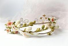 A delicate bridal crown adorned with vintage ivory blossoms and blush pink rose buds. Golden flowers with rhinestone centers and curling vines add a whimsical touch...  The base is a double band hand wrapped in beige rose ribbon with two loops at the back for fastening with bobby pins or tying ribbons through. Whichever works best for your hair style! -- double band crown -- can be worn with ribbon or bobby pins -- one size fits all -- handmade with ♡ by me -- leaves my studio in 1-2 weeks…