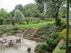 Rasenfläche, Bäume, Sträucher und Pflanzenbeete im Landhausgarten