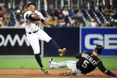 Double up:     Yangervis Solarte #26 of the San Diego Padres throws over Carlos Gonzalez #5 of the Colorado Rockies as he turns a double play during the fifth inning of a baseball game at PETCO Park on June 4, in San Diego, Calif.