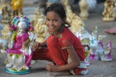 An Indian child poses while giving final touches to a statue of Hindu Goddess Lakshmi, who represents wealth, at a roadside stall ahead of D...