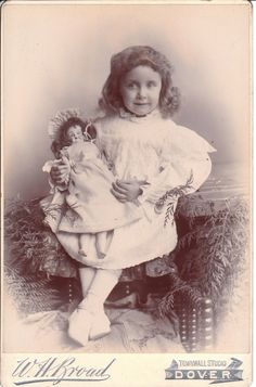 An adorable and sweet looking little girl poses with her beautiful doll in this portrait by W. H. Broad of the Townwall Studio in Dover, England. She is sitting near a careful arrangement of fern o...